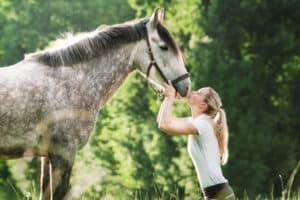 Junge Frau ksst ihr Pferd